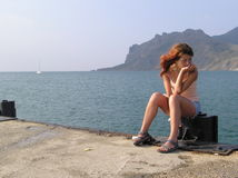 Waiting for a boat. Beautiful girl sitting at the pier waiting for a boat to come royalty free stock photos
