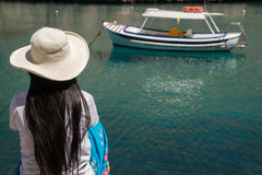 Waiting for the boat. An asian lady with a hat waits for a boat Royalty Free Stock Photography