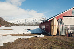 Waiting for the boat season to fish. The boat house and boats near lake covered with the ice royalty free stock photos
