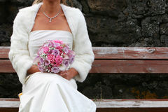 Waiting bride. Newly wedded bride sitting on bench with bridal bouqet in hands, waiting for her new husband royalty free stock images