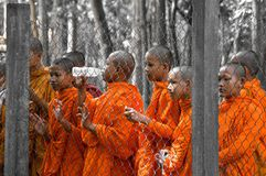 Waiting buddhism Monks behind a fence. Young Cambodian monks stood behind a demarcation and wait hopefully, Phnom Penh, Cambodia Stock Photography