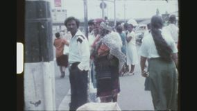 Waiting For A Bus. SOUTH AFRICA, DURBAN, MARCH 1976. South African Local Residents Waiting For A Bus On The Sidewalk Of A Fairly Busy Street stock footage