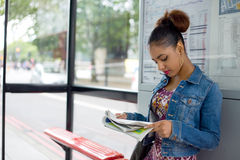 Waiting at the bus stop. Young woman reading a paper at the bus stop royalty free stock photo