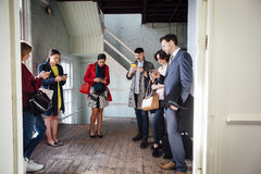 Waiting For A Business Meeting. Group of professional businesspeople are waiting outside of a meeting room. They are all engrossed in their smartphones Stock Photography
