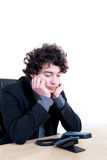 Waiting for a call. Young business man waiting a call at office on white background Royalty Free Stock Image