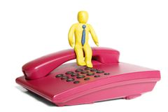 Waiting for a call. Plasticine businessman sit on a telephone stock photos