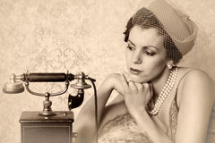 Waiting for a call. Stunning vintage 1920s woman talking on an antique telephone royalty free stock images