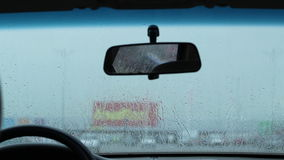 Waiting in the Car in Rain. Inside the car waiting for the rain to pass. through some of the drops on the windshield can be see the outside street traffic. Sound stock video footage
