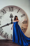Waiting for child. Young brunette pregnant woman with long beautiful hair staying near the big clock in long blue dress Stock Photos