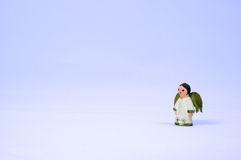 Waiting for christmas. Little painted wooden anglel standing in a blue void royalty free stock image
