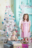 Waiting for Christmas: a little girl dresses up Christmas tree Royalty Free Stock Photos