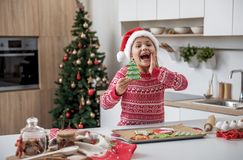 Joyful little girl having fun in kitchen on holiday. Waiting for Christmas miracle. Portrait of excited female kid showing cookie is shape of Christmas tree and Royalty Free Stock Image
