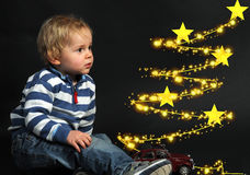 Waiting for christmas. Toddler boy is waiting for christmas fascinated by a tracer Stock Image