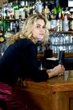Waiting on a date. Beautiful blond woman in her late twenties sits at the bar, looking around, waiting for her date to show up Royalty Free Stock Photo