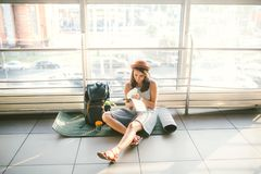 Waiting, delayed transport in the terminal of the airport or train station. Young caucasian woman in dress and hat sits on tourist royalty free stock images