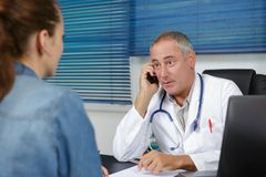 Waiting for doctor to finish conversation. Waiting for the doctor to finish his conversation Stock Photos