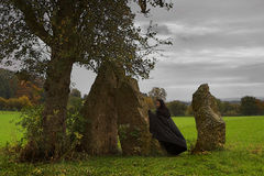 Waiting for the druids. Woman or witch in black cape walking around a group of manhirs and a solitary tree stock photos