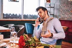 Waiting for fiancee. Man is speaking by smartphone while waiting in restaurant. His girlfriend. Red roses are lying on the table royalty free stock photo