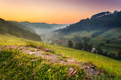 Waiting for the first rays. Stony hill among green lawn near the village, away from the forest in the mountains, foggy summer morning before sunrise Royalty Free Stock Image