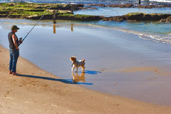 Waiting for the fish. Fisherman with rod and line and a small dog on Mediterranean Sea stock images