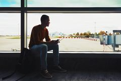 Waiting for a flight. Silhouette of the young man with mobile phone and boarding pass in hand waiting inside airport terminal for airplane royalty free stock images