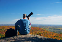 Waiting foe the shot. Male photographer shooting at the top of a mountain stock images