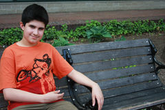 Waiting for a Friend. Latino teenager sitting on a bench, inviting a friend to sit next to him. He is friendly and just wants company Stock Photo