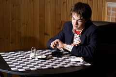 Waiting for a friend. Young guy in dark suite waiting for a friend in cafe. Sit near checkered table, look at the watch Royalty Free Stock Photography