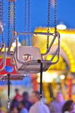 Waiting for Fun. A seat on an amusement park ride sits vacant, suspended by chains, waiting for a rider Royalty Free Stock Image