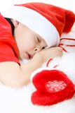 Waiting a gift. Little boy in Santa's hat sleeping and clench one's fist with christmas sock. Upper part of image isolated stock photo