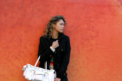 Waiting girl. The girl dressed in black with white handbag on orange Royalty Free Stock Photos