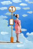 Waiting. A girl waiting for a suitor at a bus stop in the clouds Stock Photography