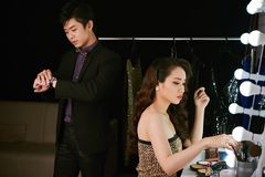 Waiting for girlfriend. Vietnamese young men waiting when his girlfriend applying make-up in front of mirror Royalty Free Stock Images