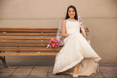 Waiting for the groom. Gorgeous young bride sitting on a bench outdoors and waiting for the groom Stock Image