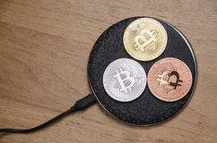 Bitcoin coins on wireless recharging Stock Image