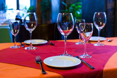 Waiting guest concept. Served Table with red and orange tablecloth, wine glasses, white plates and cutlery Stock Photography