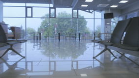 Waiting hall of the airport. The camera moves backward. The action takes place at the airport, in the waiting hall. Handsome businessman wearing the suit sits in stock video footage