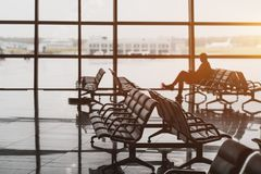 Waiting hall in airport terminal with male silhouette. Waiting room in airport terminal departure area near gates: hall with rows of armchairs, glass facade Stock Photo