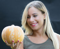 Waiting halloween. Young woman watching with an amused expression  the pumpkin that will prepare for Halloween Stock Photography