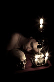 Waiting. The head of a young girl lying beside to the skull and candlestick. Shutter speed 30 sec Stock Photo