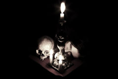 Waiting. The head of a young girl lying beside to the skull and candlestick. Shutter speed 30 sec Stock Photography