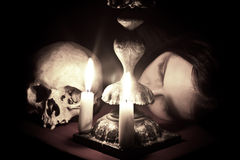 Waiting. The head of a young girl lying beside to the skull and candlestick. Shutter speed 30 sec Stock Images