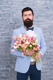 Waiting for his girlfriend. Romantic man with flowers. Romantic gift. Macho getting ready romantic date. Tulips for. Sweetheart. Man well groomed wear blue royalty free stock image