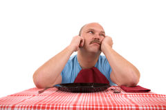 Waiting for his meal. Overweight man looking very unhappy with empty plate in front of him royalty free stock photography