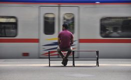 Waiting for his train to come. A guy waiting and sitting in a train station Royalty Free Stock Photography