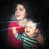 Waiting at home window. Happy mother and baby daughter waiting at home window stock photo