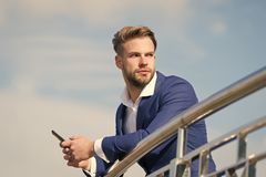 Waiting important call from partner. Businessman use smartphone for video call or texting sky background. Man in suit. Businessman takes advantages of modern royalty free stock image