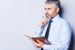 Waiting for inspiration. Thoughtful mature man in shirt and tie touching his chin with hand and looking away while holding note pad and standing against grey Royalty Free Stock Photos