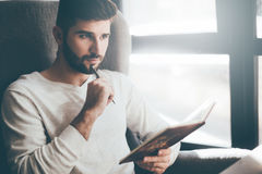 Waiting for inspiration. Thoughtful young man holding notebook and touching his chin with pen while sitting at his working place in office Royalty Free Stock Image