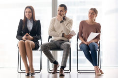 Waiting for job interview. Worried and nervous applicants sittin Stock Image